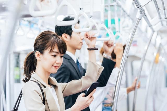 スマホを使う通勤中の女性
